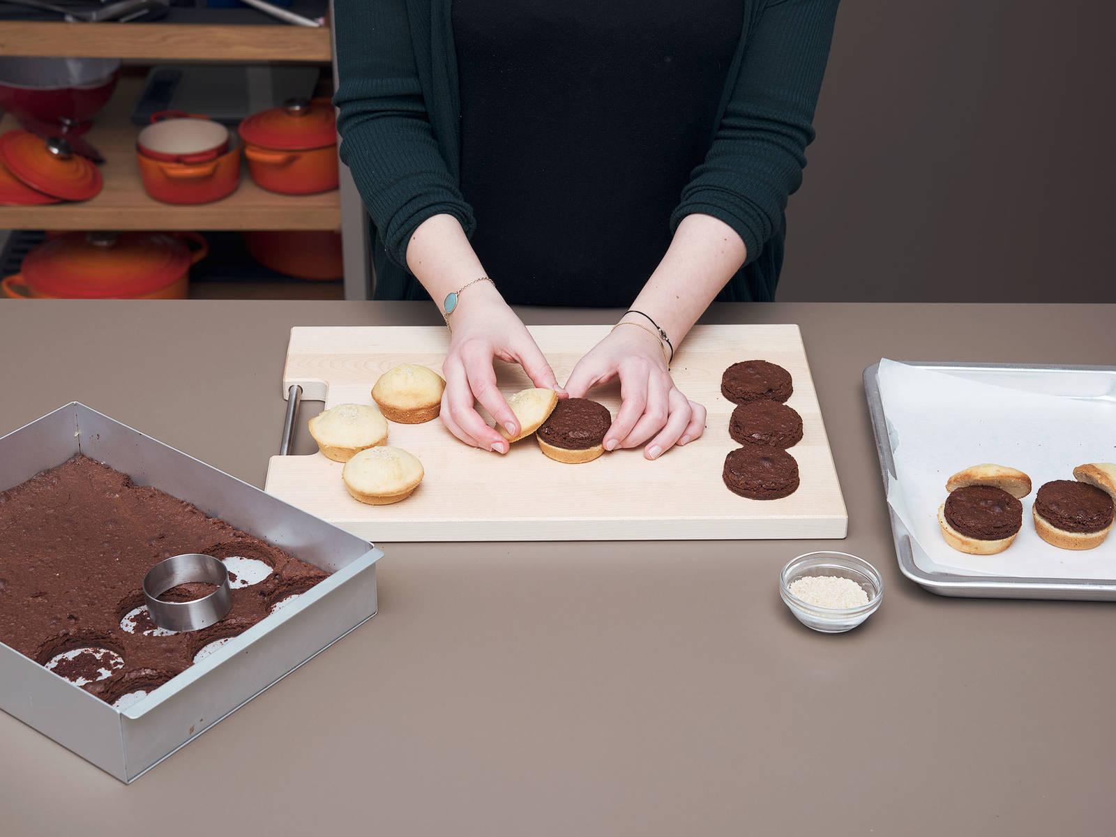 """Mit einer runden Ausstechform oder einem Glas runde """"Burgerpatties"""" aus den Brownies ausstechen. Für das Burgerbrötchen die Muffins mit einem scharfen Messer quer in zwei Hälften teilen. Die Oberseite des Muffins mit Sesam bestreuen. Browniepattie auf die untere Muffinhälfte setzen."""