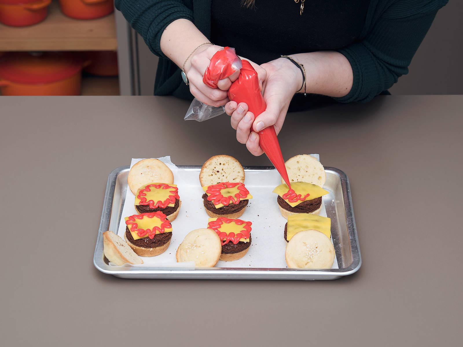 Für den Zusammenbau der Burger, die Mango-Quadrate als Käsescheiben auf die Browniepatties legen. Mit dem roten Frosting kreisförmige oder blumenähnliche Formen am Rand entlang spritzen.