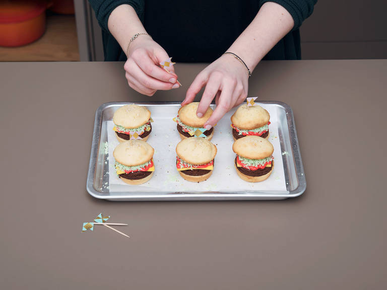 Sprinkle green coconut flakes on top of red frosting. Place bun tops on top of each burger and secure with cupcake picks. Enjoy!