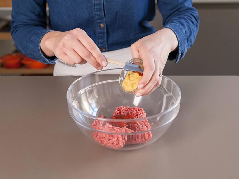 将绞细牛肉、第戎芥末酱和番茄酱加入搅拌容器中。加入盐和黑胡椒搅拌均匀。将肉末分成两半后用手捏成肉饼。