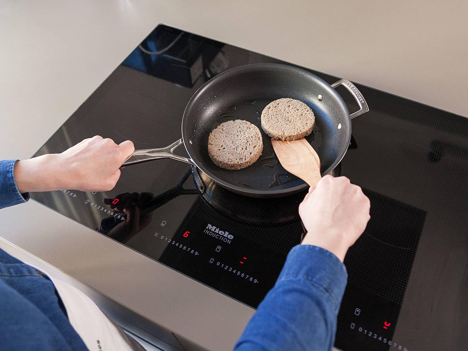 用蛋糕模具压制出两片接近肉饼大小的面包用以准备汉堡。以油热锅,用中火煎面包片至酥脆。
