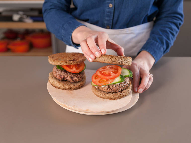 Top rye bread slices with mayonnaise, burger patties, and slices of tomato and cucumber. Enjoy!