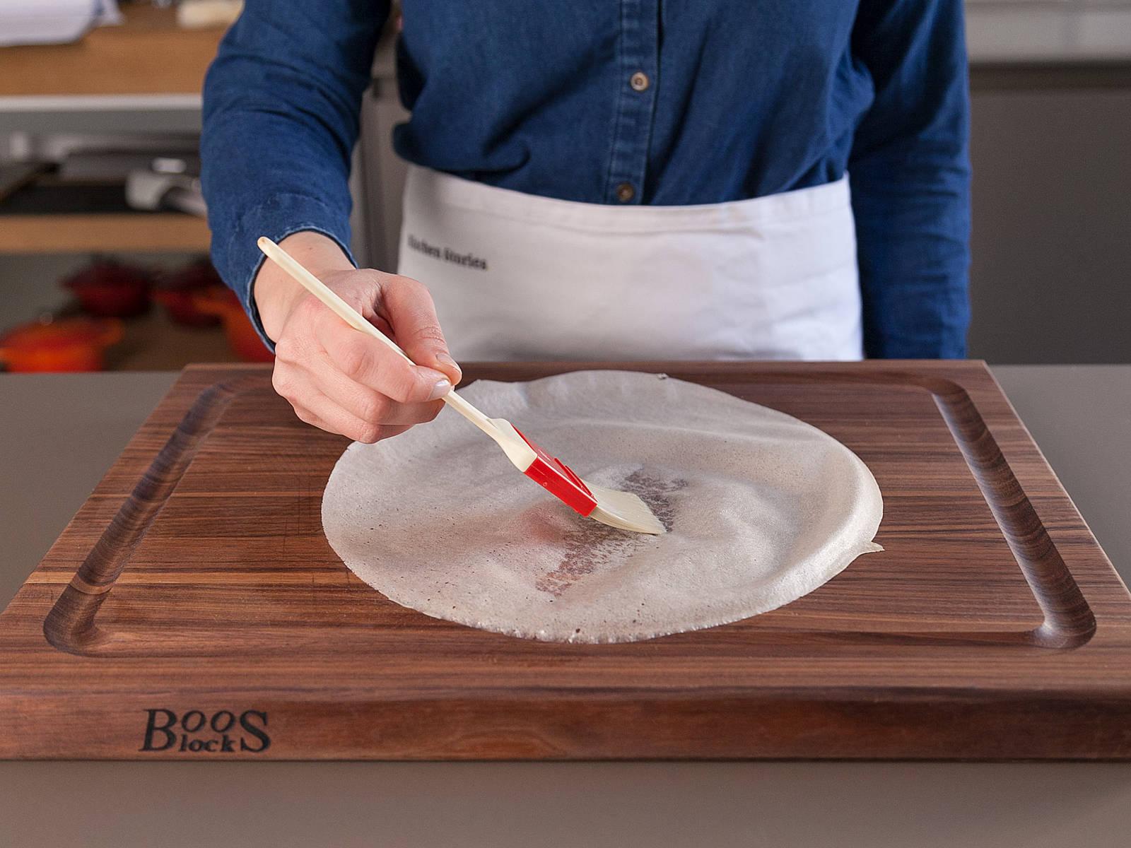Brickteig mit Eiweiß einpinseln. Je eine Scheibe Camembert auf ein Blatt Brickteig legen. Die Seiten umschlagen, damit der Camembert von allen Seiten verschlossen ist.