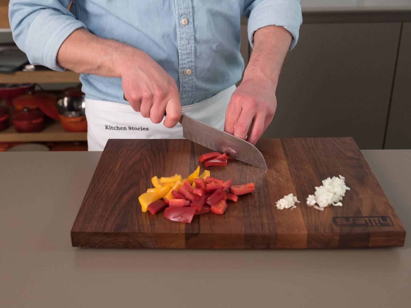 Zwiebel und Knoblauch schälen und fein würfeln. Paprika in mundgerechte Stücke schneiden. Garnelen und Tintenfisch vorbereiten.