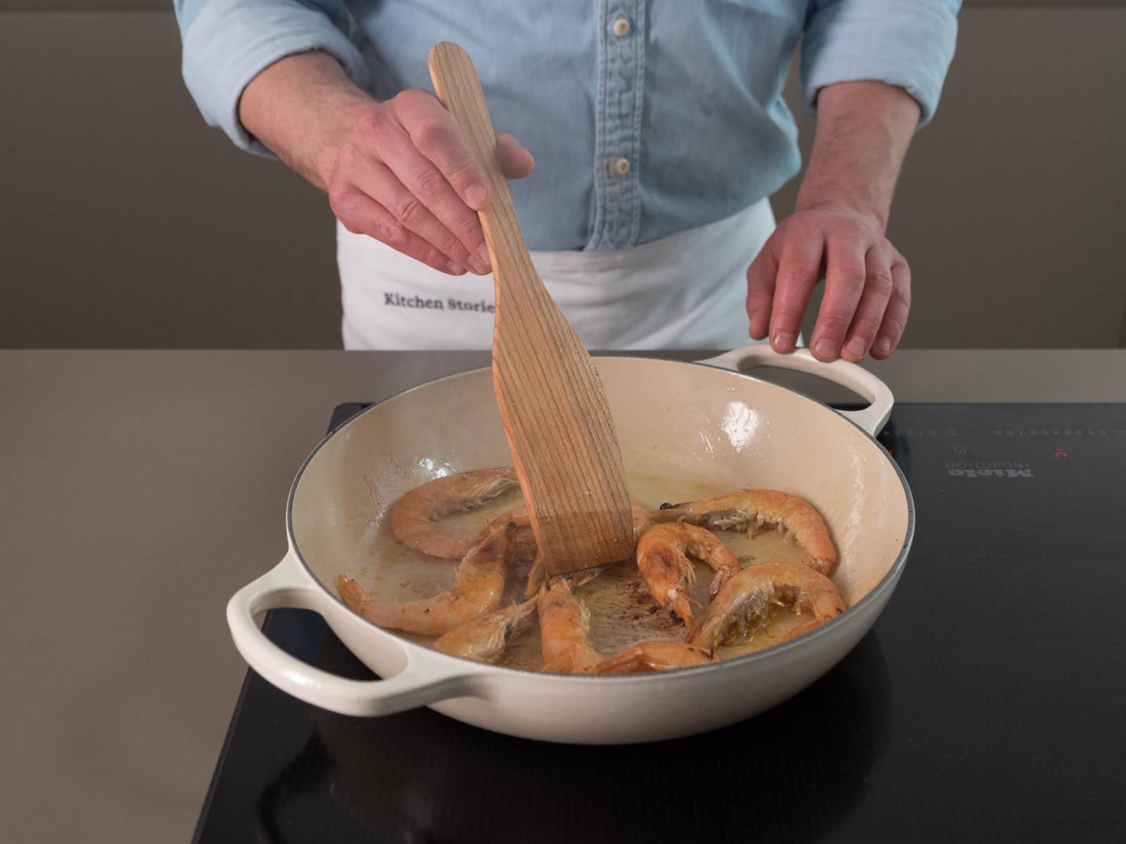 Öl in einer großen Pfanne erhitzen. Garnelen und Tintenfisch ca. 5 Min. braten, danach herausnehmen und beiseitestellen.