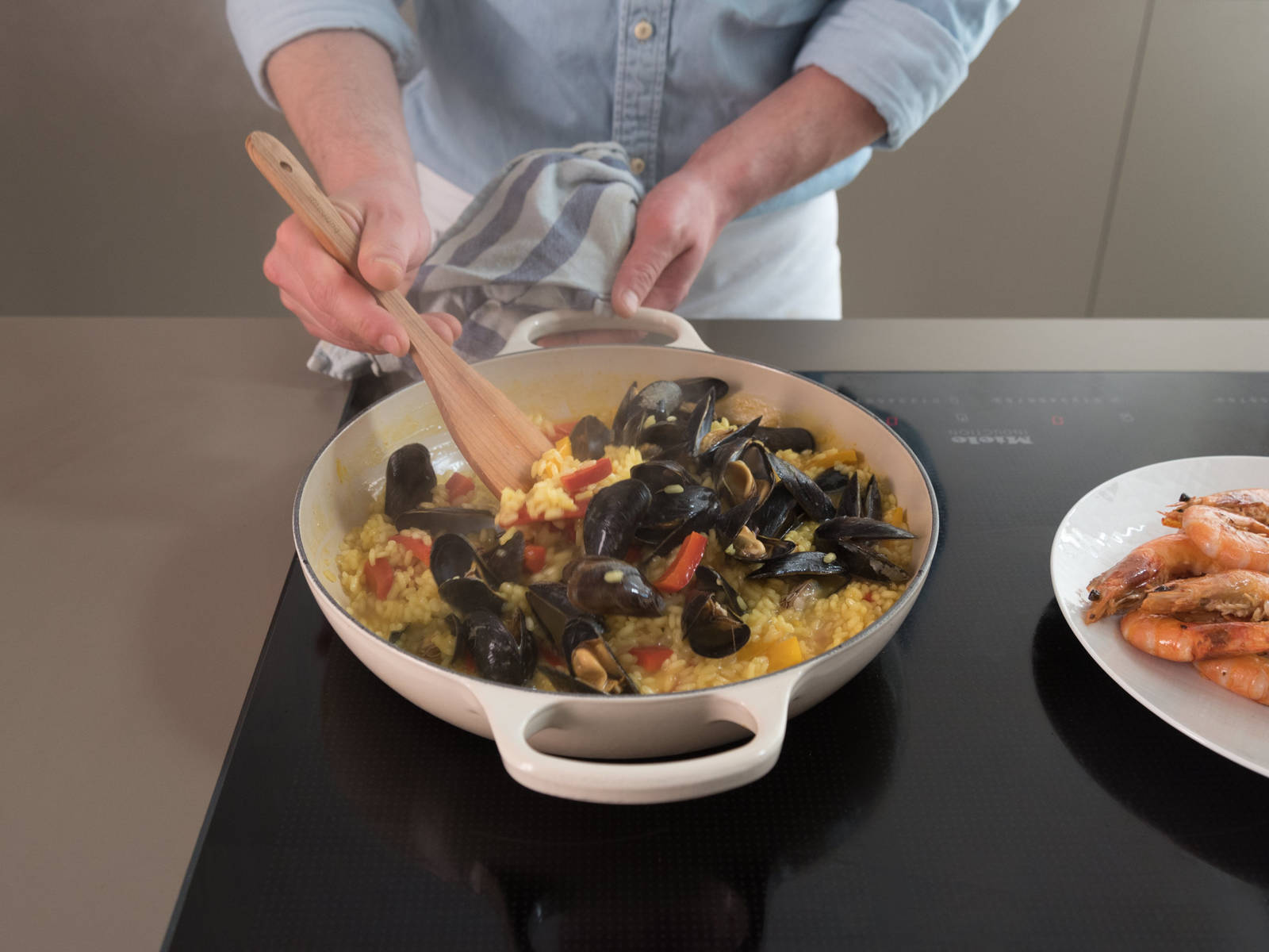 Turn down heat to medium-low and keep simmering until almost all liquid is absorbed. Add mussels, cover with lid, and simmer for approx. 5 min. Afterwards, add prawns and squid and keep simmering uncovered for approx. 5 more min., or until liquid is completely absorbed. Stir in peas.