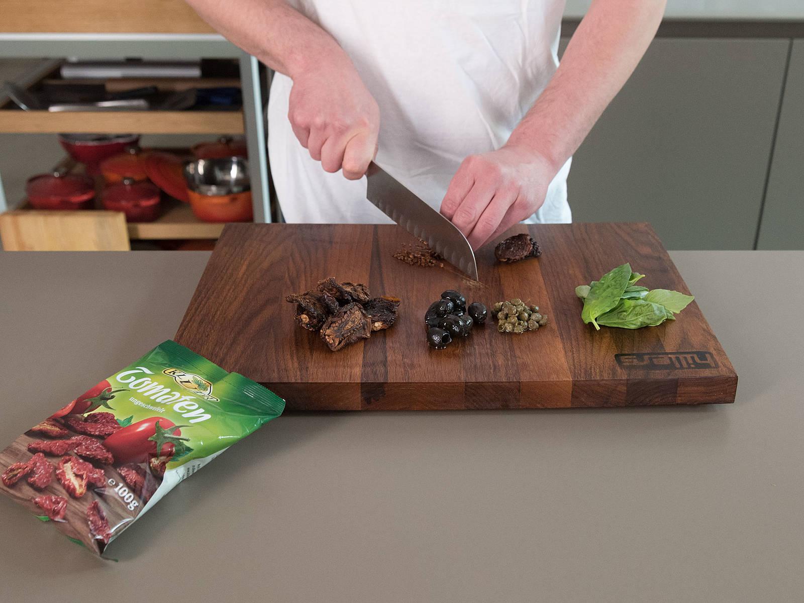 Schwarze Oliven, Kapern, getrocknete Tomaten und Basilikum fein hacken.