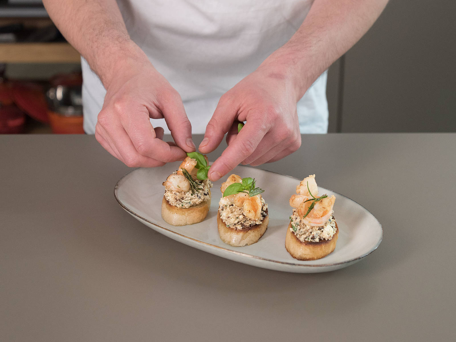 Spread feta cream on toasted baguette slices, top with fried prawns, and serve with more basil. Enjoy!