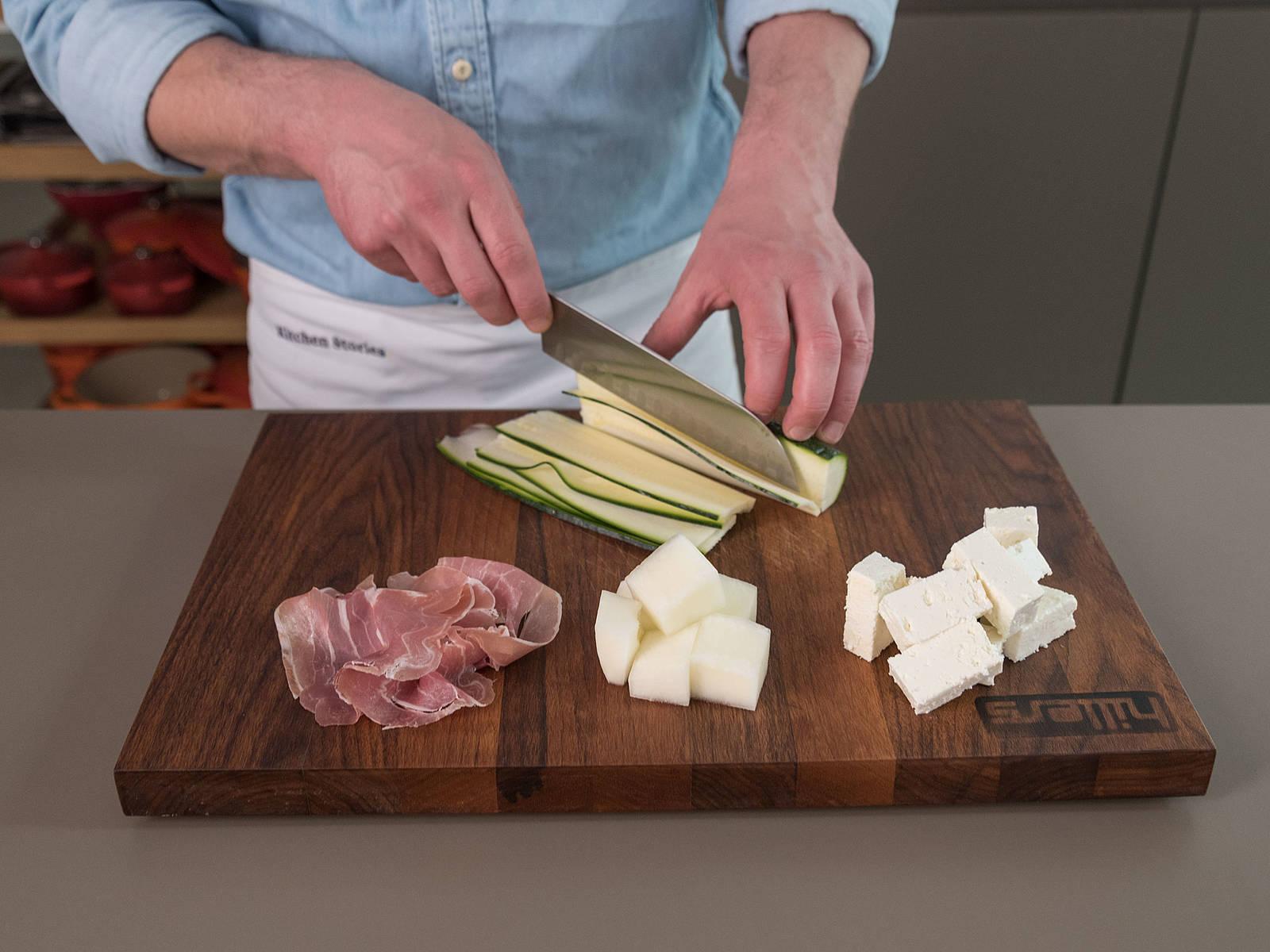 菲达芝士和哈蜜瓜切成大小均匀的小块。西葫芦竖着切成薄片。