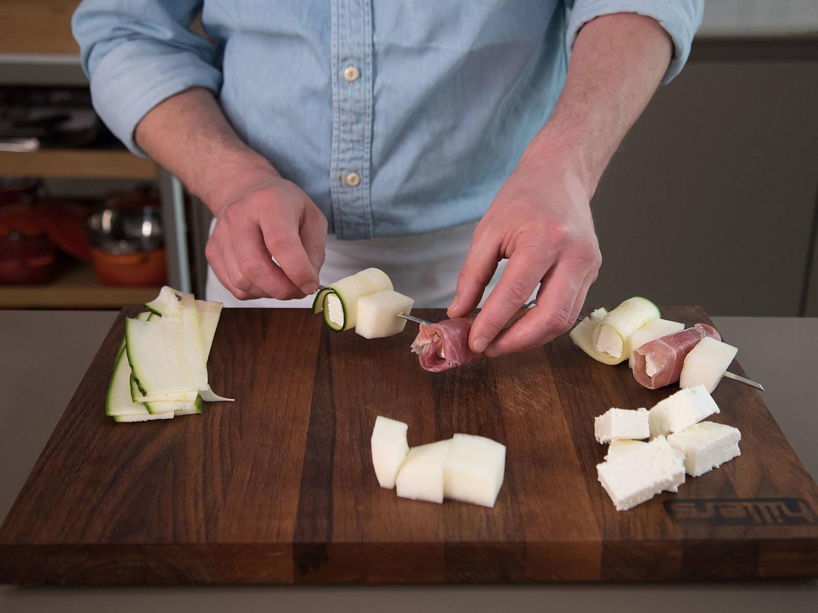 将西葫芦菲达卷、熏火腿菲达卷和哈密瓜块依次插到木叉上。
