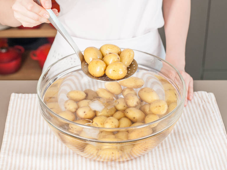 Boil potatoes in salted water until tender. Transfer them to ice bath to chill for a few minutes, then drain and pat dry. Halve or quarter potatoes (depending on size) and place in a large bowl.