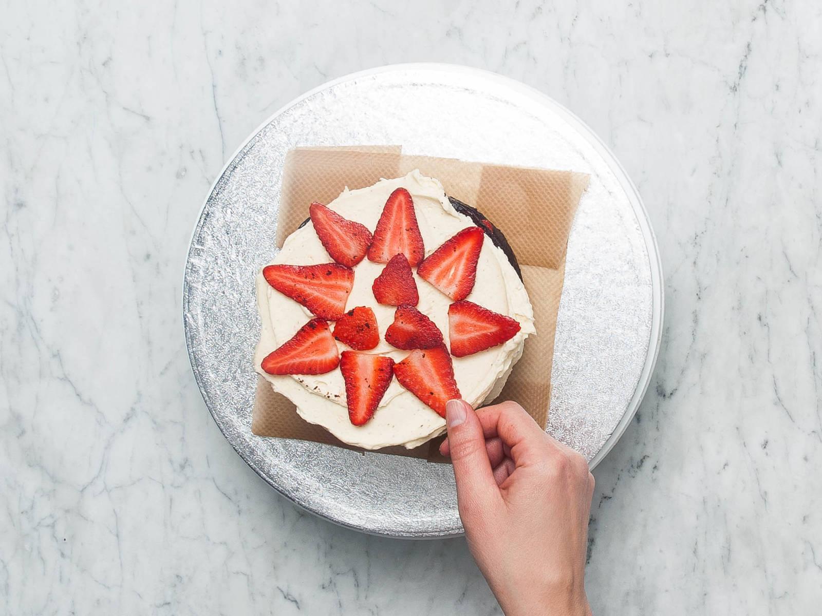 如有需要,可用锯齿刀将蛋糕顶部稍微切去,使其平整。将一层蛋糕放到盘子中,均匀地将些许奶油糖霜抹上去。放上一层草莓,然后盖上第二层蛋糕。重复操作,最后放上第三层蛋糕。冷藏15-30分钟,或直至蛋糕冰凉且结实。
