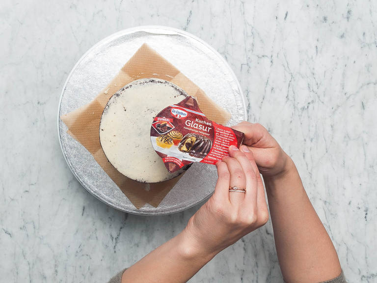 """Thinly coat cake with remaining frosting, letting the chocolate cake peek through to achieve a """"naked"""" look. Prepare chocolate glaze according to package instruction, then drip it over one of the edges of the cake. Garnish with strawberries and add writing, if you like. Enjoy!"""