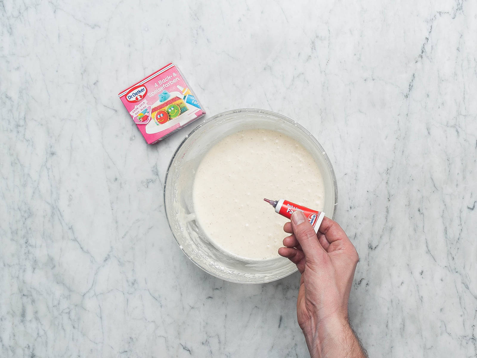 与此同时,制作糖霜:将法式酸奶油、糖和香草糖放到一个中号搅拌碗中。搅打至完全混合,并稍微变稠。放入一或两滴食用色素,直至调出理想的粉色。搅拌均匀。