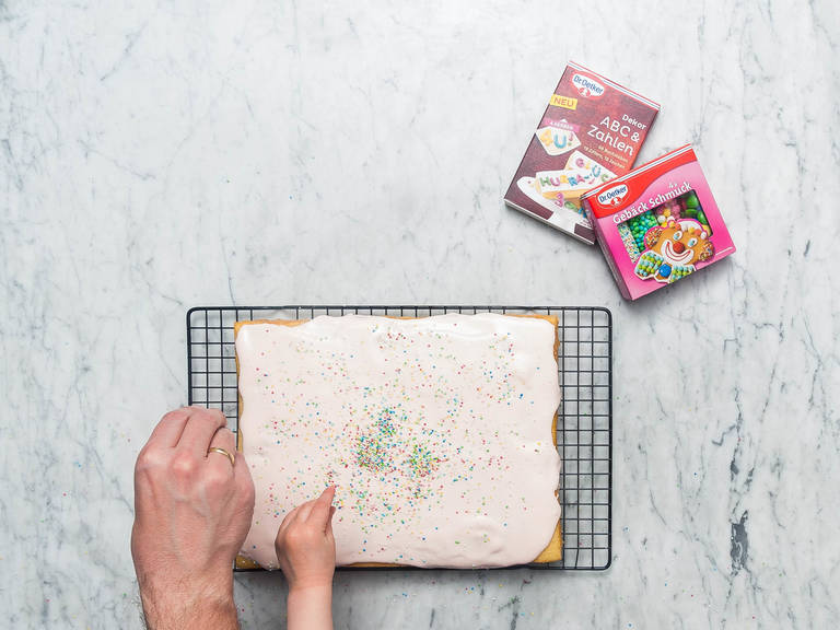 Crème über den Kuchen glattstreichen und nach Belieben mit Streuseln und Buchstaben dekorieren. Guten Appetit!