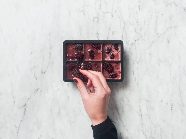 将西瓜汁倒满冰膜的2/3高度。每格放入一颗冰冻黑莓。冷冻6小时,或直至完全冻上。