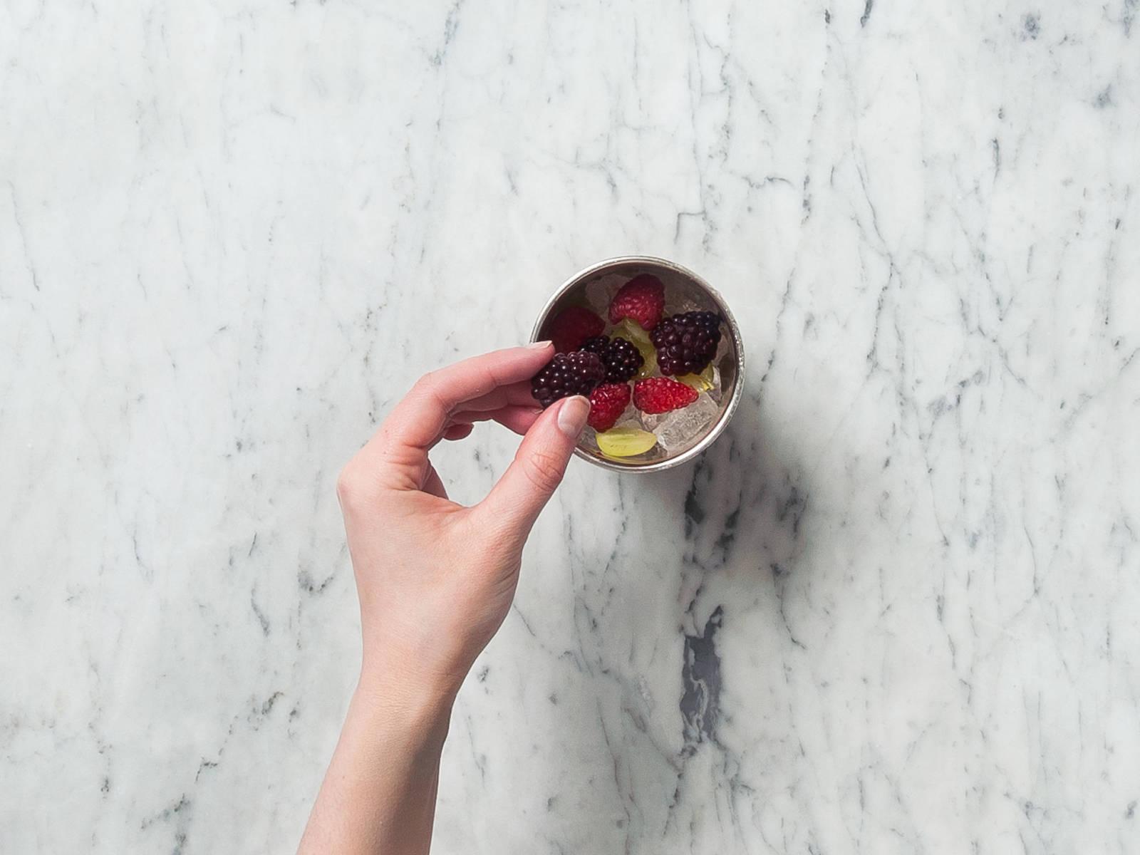 如有需要,可将当季水果切半。将刨冰放到玻璃杯中。放上处理好的水果。