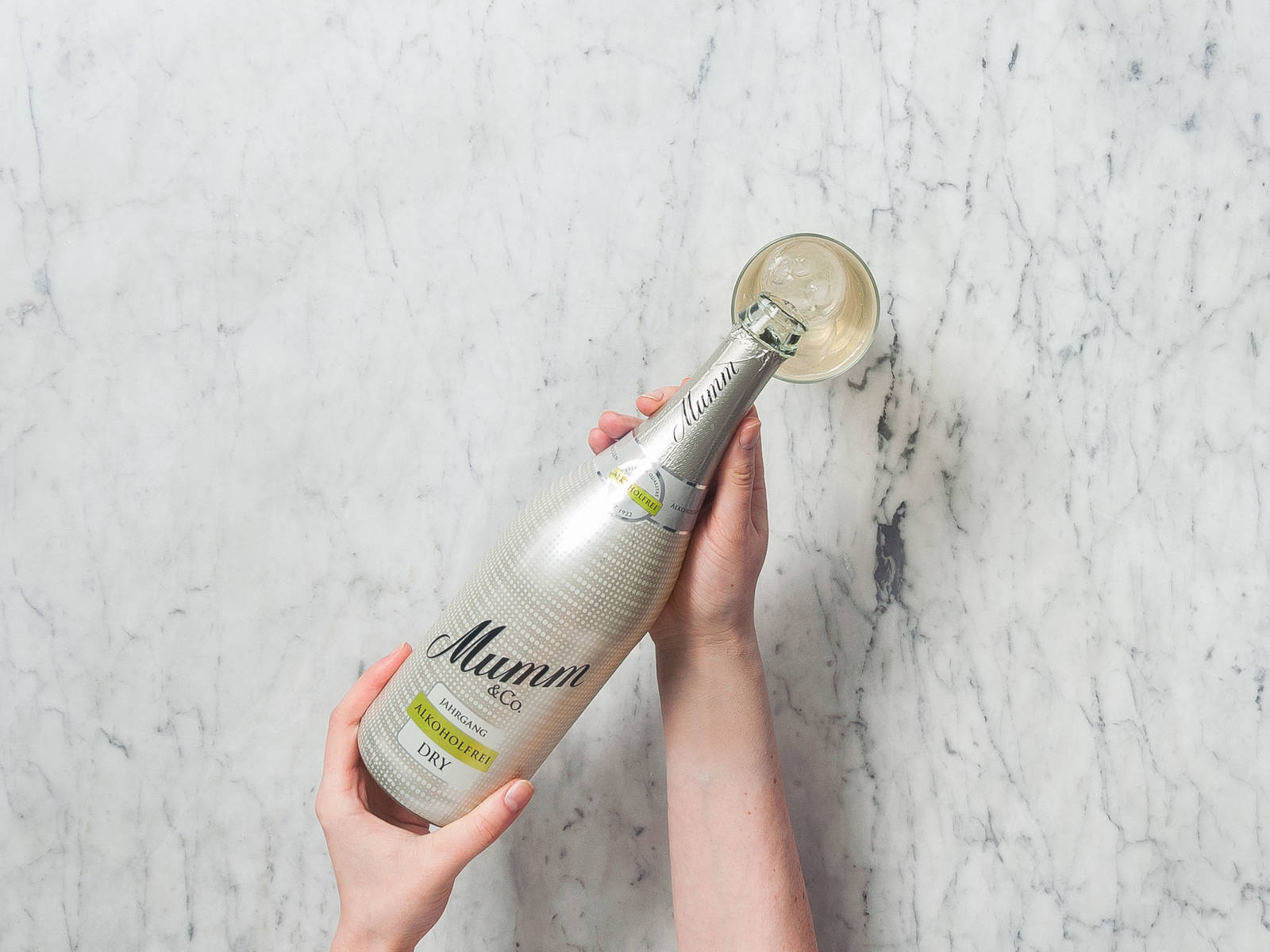 Fill glass with sparkling water and non-alcoholic sparkling wine. Garnish with fresh rosemary and lemon peel. Cheers!