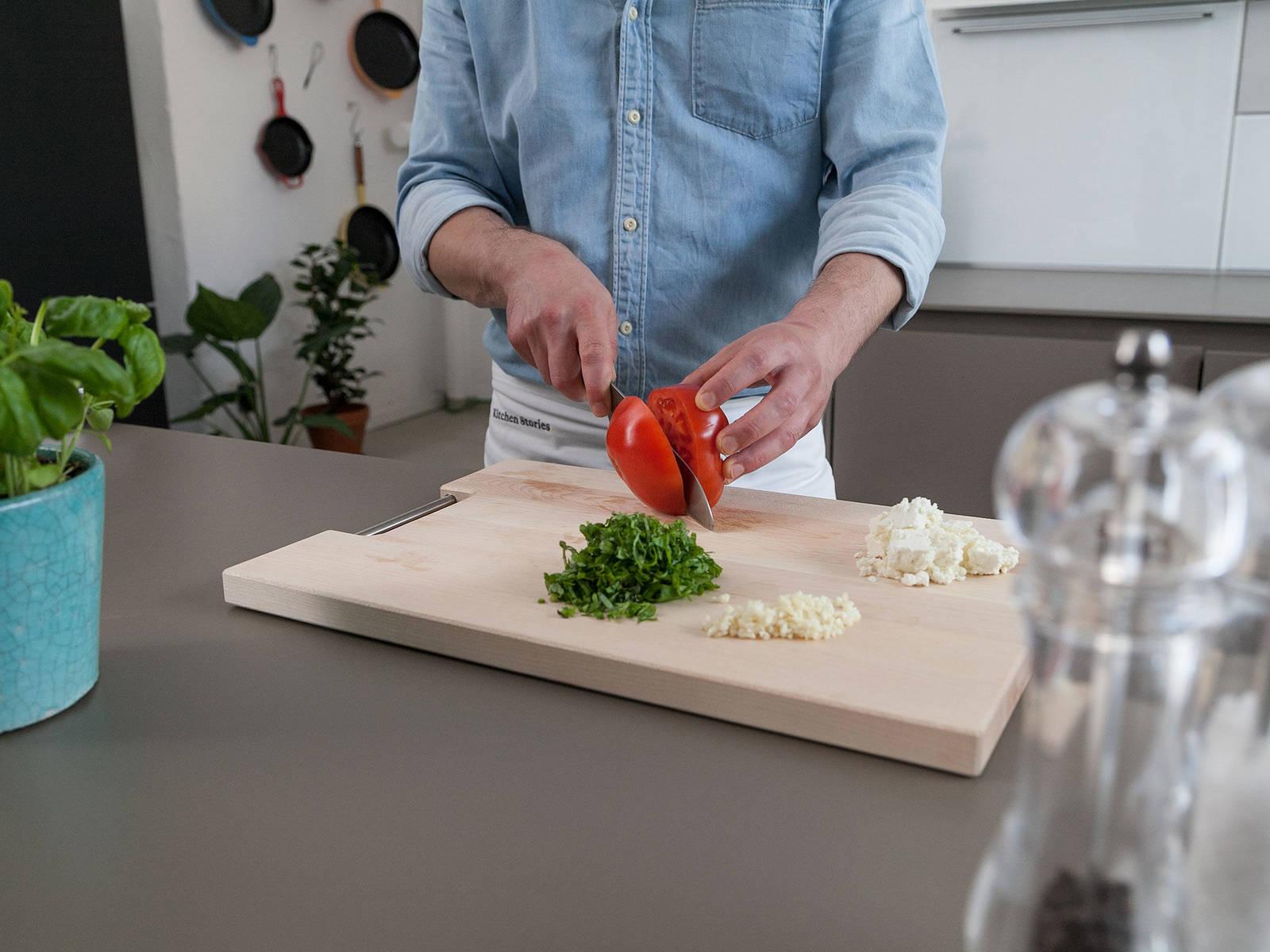 清洗番茄,交叉切半。蒜剥皮后剁碎,切碎罗勒叶。菲达芝士捏碎。