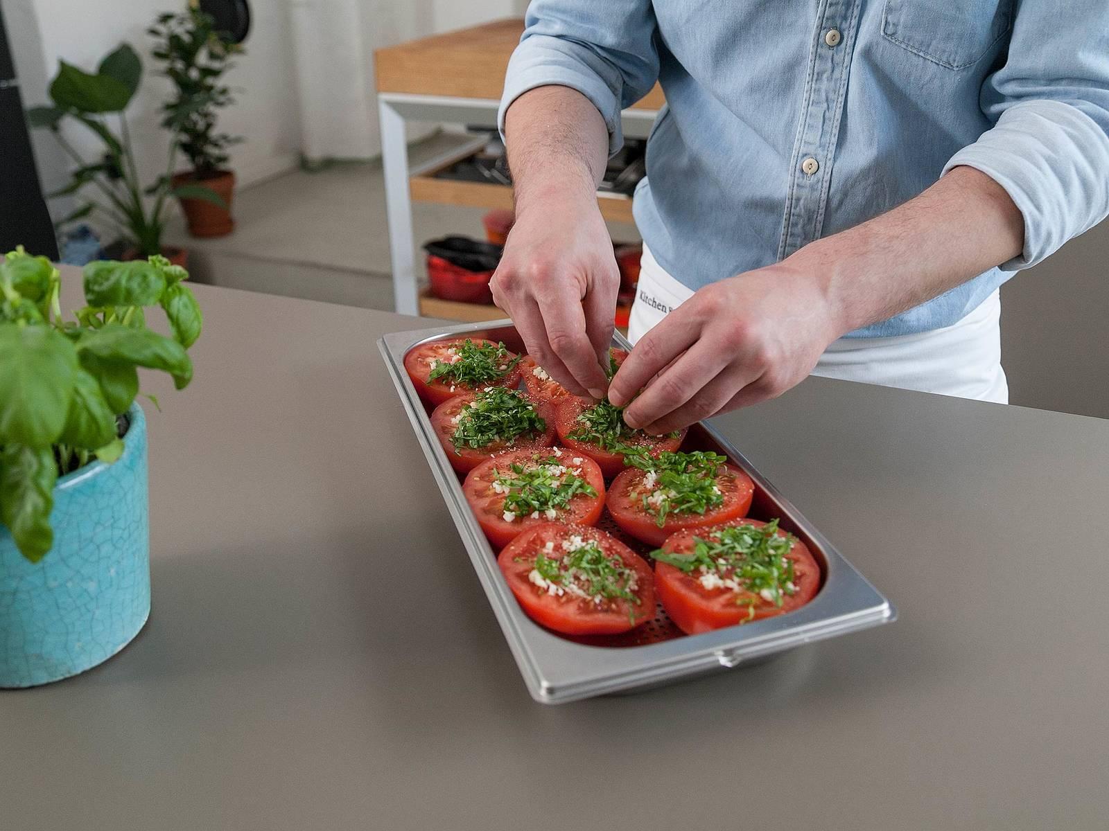 将切半的番茄放到蒸煮容器中,切面朝上。撒上蒜末,撒盐与胡椒调味,铺上罗勒叶和菲达芝士。