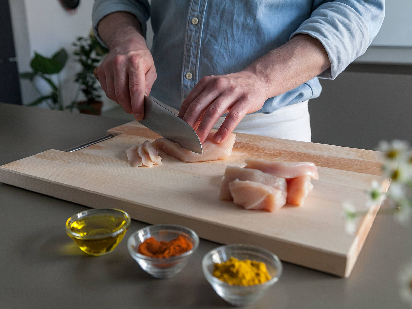 Slice chicken breasts crosswise. Mix olive oil, spicy paprika powder, and curry powder in a bowl. Add  chicken breast slices, toss to coat, and let marinate for approx. 15 min.