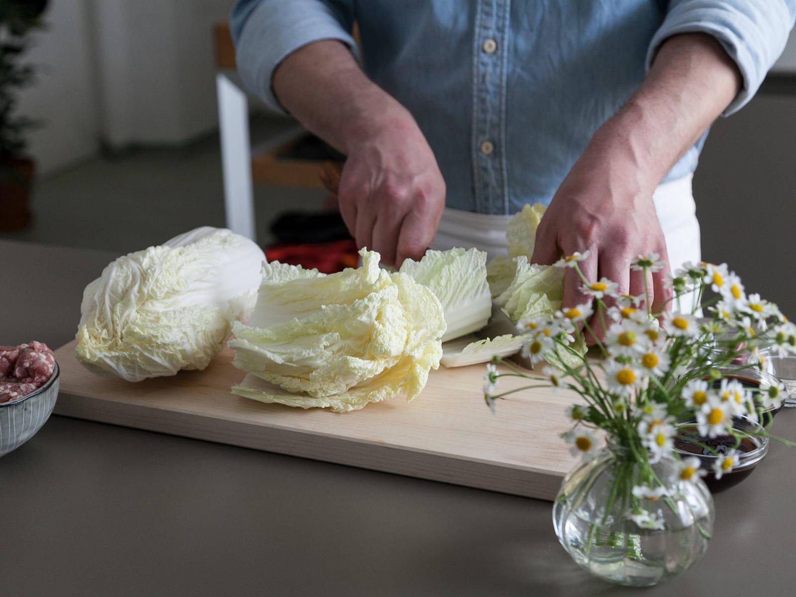 蒜剥皮剁碎,置于一旁。青葱切段后置于一旁。洗净大白菜,切去茎,掰掉外围的干叶片。根据需要的尺寸,掰出整片的叶片用于做卷。将白菜芯剁碎。