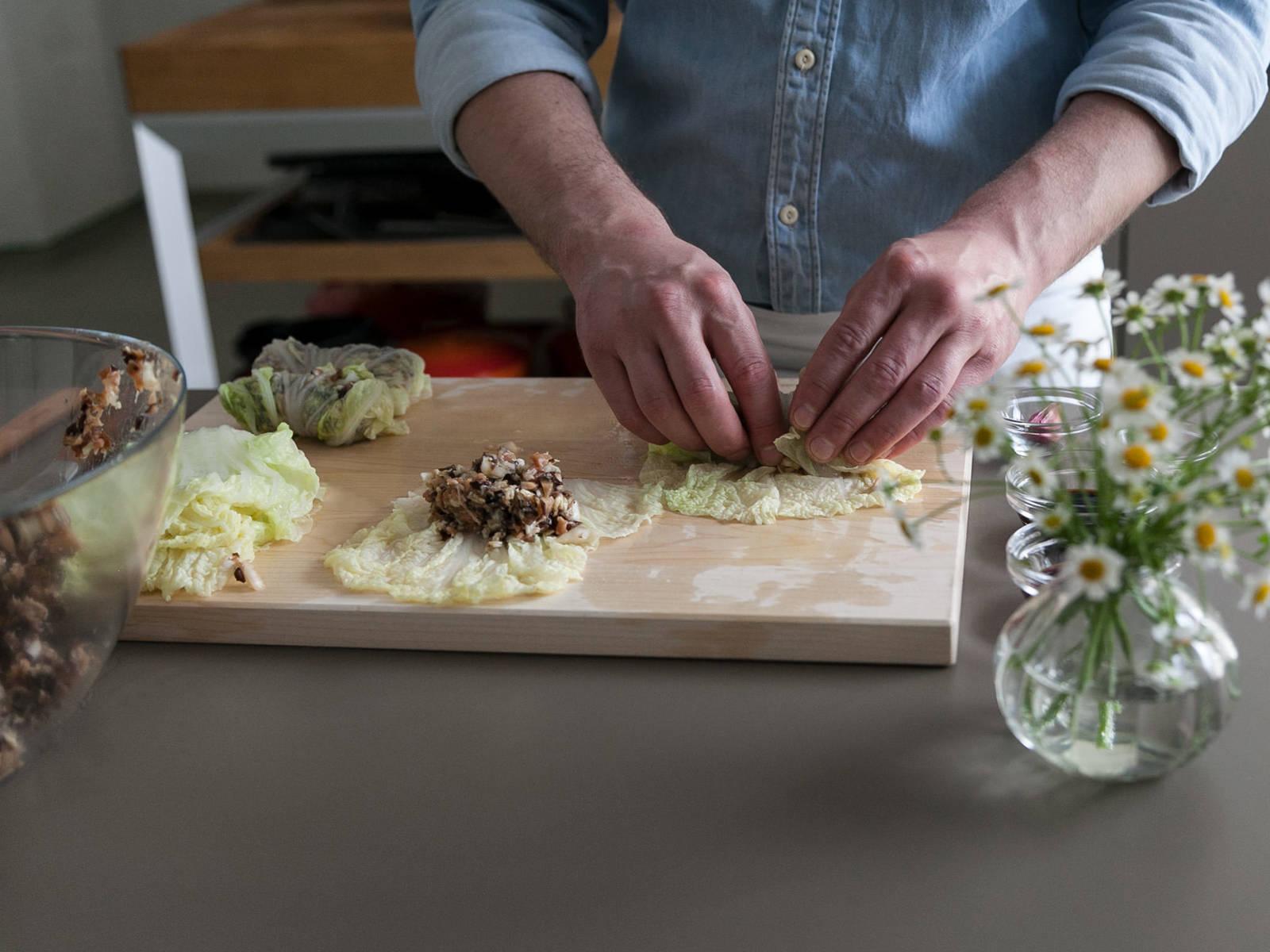 将焯过水的白菜叶放到一个干净的工作台面上铺开,每片放上两勺馅料。从底部卷起,两侧都叠起来,好让馅料充分裹好。若喜欢,可用牙签固定。重复操作直到馅料用完。