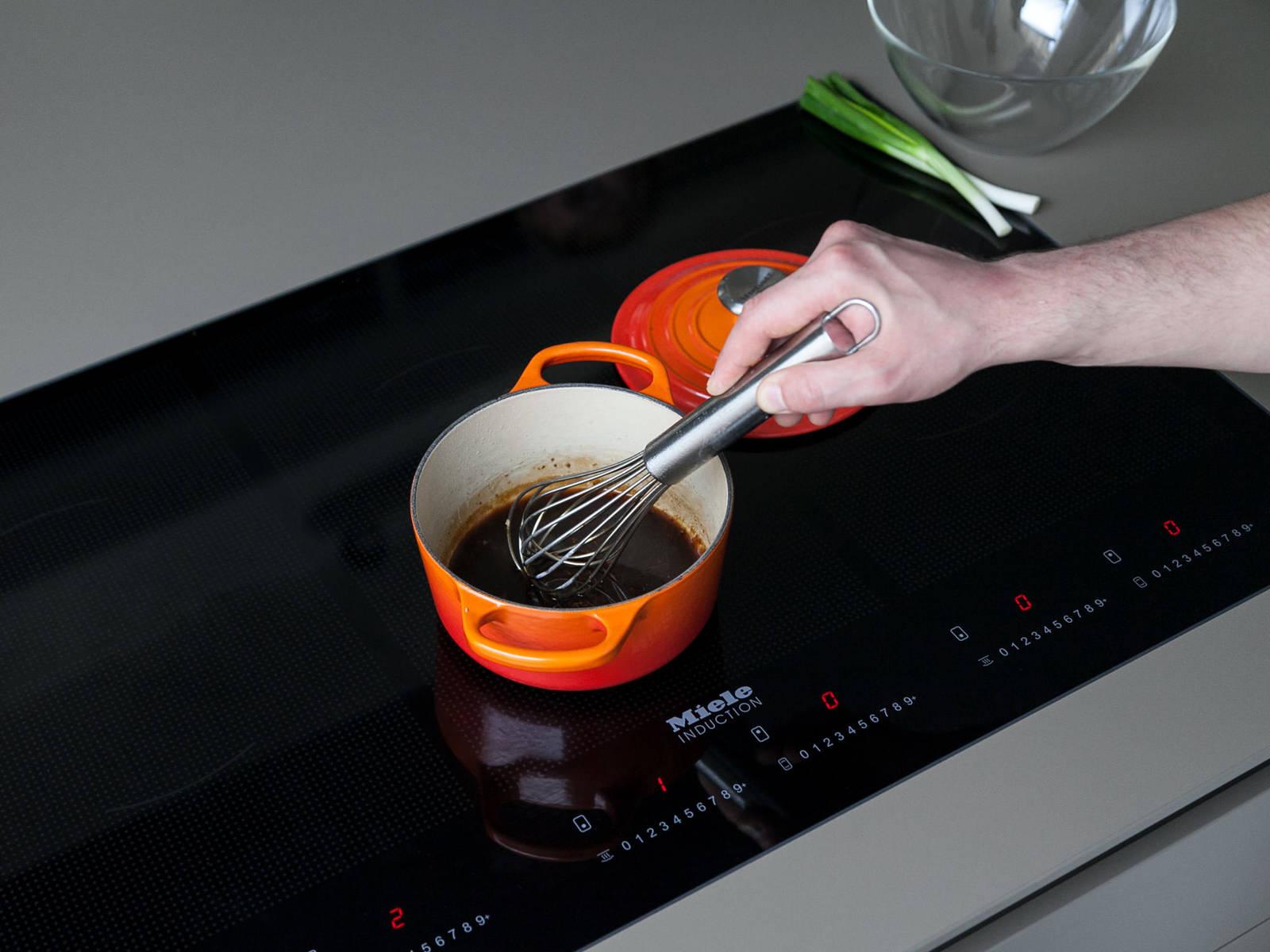 在小平底锅中热油。小火翻炒蒜末2分钟,直至发出香味。倒入汤汁、剩余的生抽、蚝油和淀粉,煨5分钟。在白菜卷上撒青葱,倒上酱汁,搭配米饭。尽情享用吧!