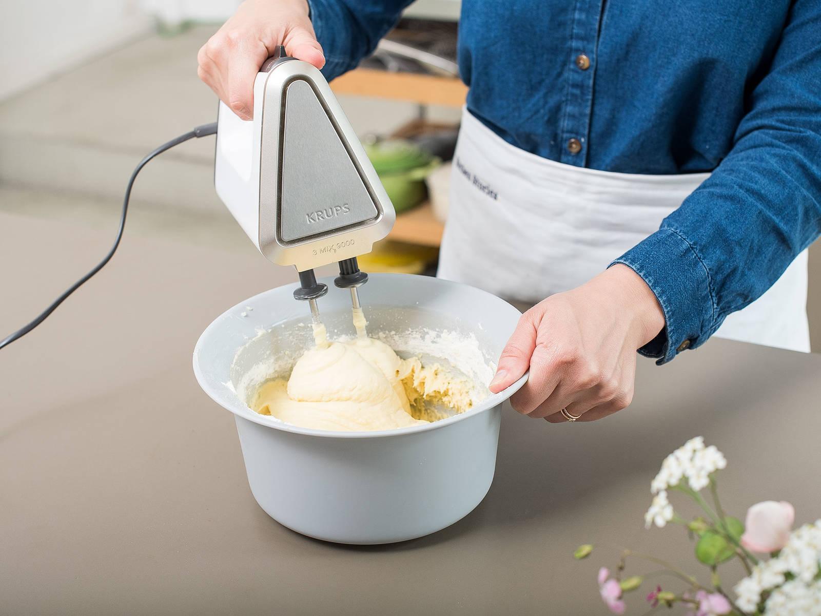 在一个大搅拌碗中,混合黄油、糖和盐,搅打至质地轻盈发泡。一次一颗地打入鸡蛋,搅打混合。加入香草精,搅拌均匀。将面粉、淀粉和泡打粉混合,和牛奶一起倒入黄油混合物中。稍微搅拌。