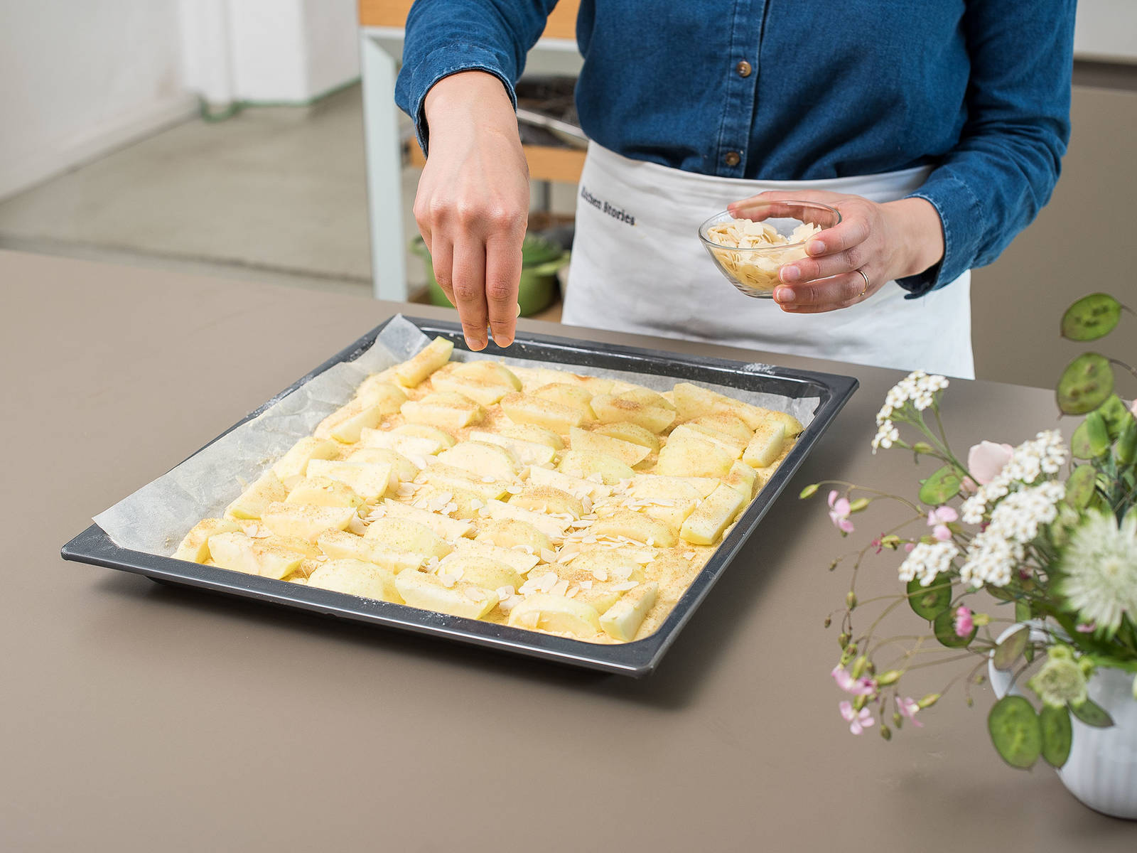 Spread the batter evenly over the prepared baking sheet, distribute apples on top, and sprinkle with almond flakes.
