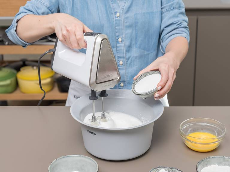 Backofen auf 190°C vorheizen. Eier trennen. Eigelb in einer kleinen Schüssel mit einer Gabel aufschlagen. Eiweiß in eine große Schüssel geben, Salz dazugeben und steif schlagen, bis sich Spitzen in der Sahne formen. Einen Teil des Zuckers langsam dazugeben und ca. 1 - 2 Min. weiterschlagen.  Die verquirlten Eigelbe vorsichtig mit einem Schneebesen unter den Eischnee heben.