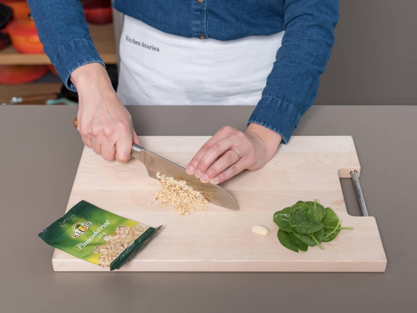清洗嫩菠菜后滤干。大略剁碎松子。蒜削皮后切片。在煎锅中,中火烘烤松子,然后置于一旁备用。根据包装说明煮通心粉,约需13-14分钟。