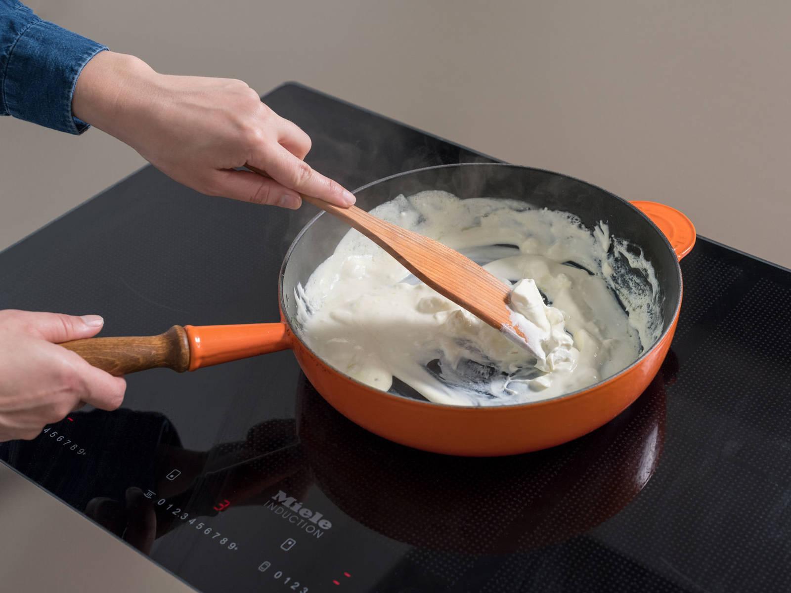 过滤通心粉,留下些许煮面水。在煎锅中,中火加热橄榄油,放入蒜翻炒。调至小火,倒入法式酸奶油和些许山羊芝士,搅拌至均匀混合。