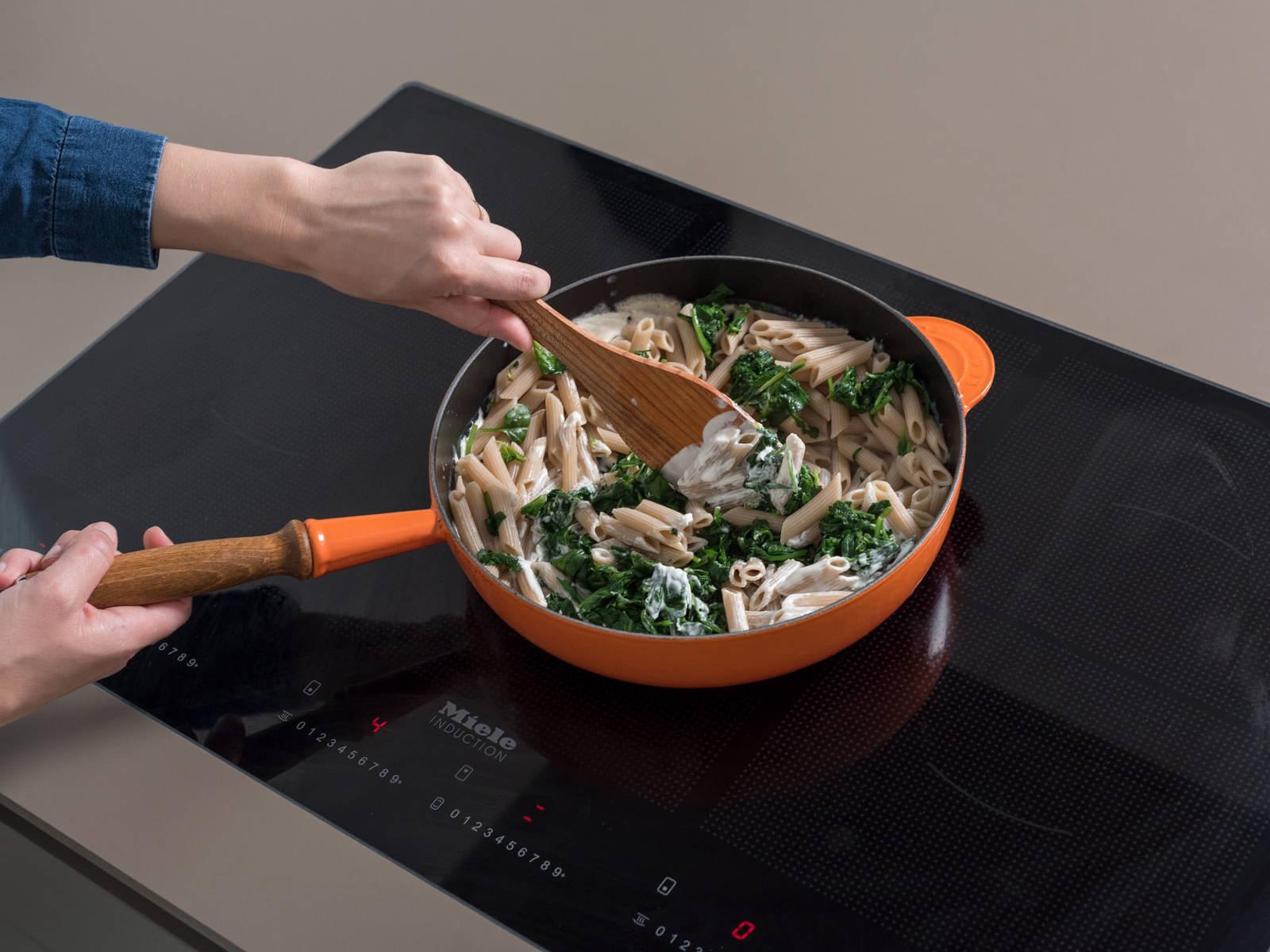 将菠菜和通心粉放到煎锅中,一同搅拌。加入几汤匙留好的煮面水,将汤汁调节至适合的稠度。撒盐与胡椒调味,撒上烤好的松子末、更多山羊芝士块和帕马森干酪。尽情享用吧!