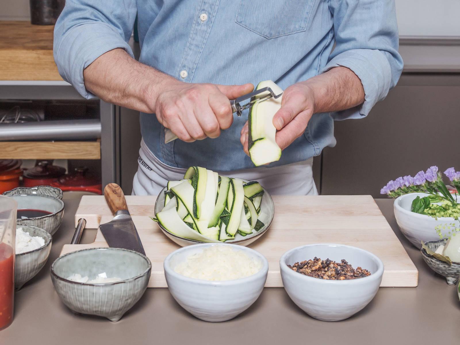 Zwiebel und Knoblauch schälen und fein hacken. Getrocknete Tomaten klein schneiden. Zucchini der Länge nach in dünne Scheiben schälen.