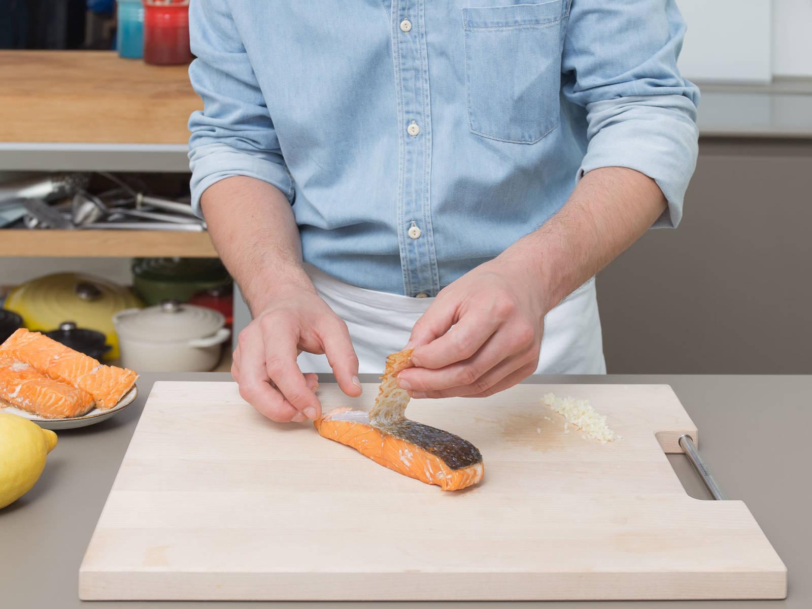 蒜削皮并剁碎。清洗菠菜,甩干,然后大略剁碎。三文鱼切皮,然后切成小块。