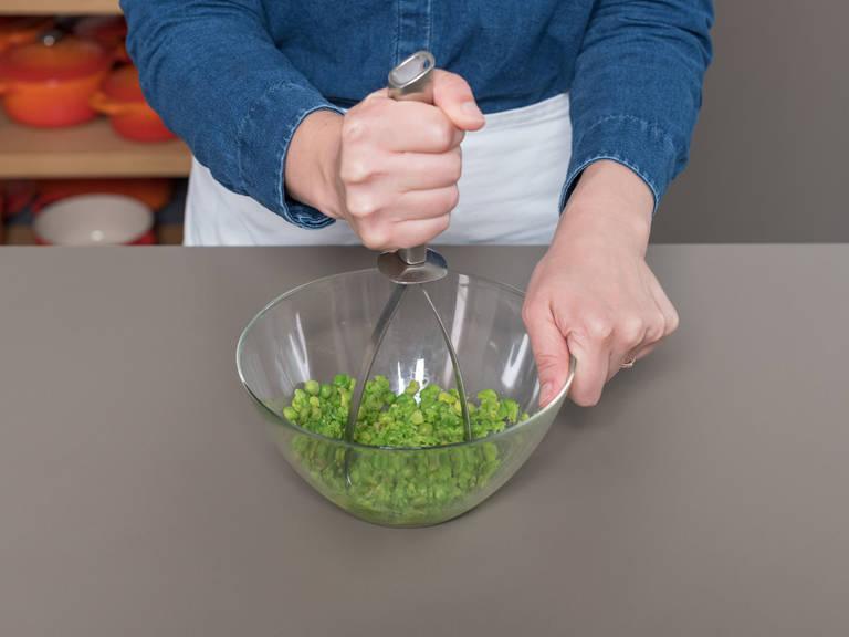 In einer großen Schüssel Erbsen ca. 2 Min. in kochendem Wasser auftauen lassen. Abgießen und mit einem Kartoffelstampfer grob zerstampfen.