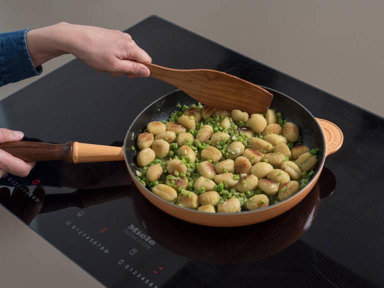 Gehackten Knoblauch zu den Gnocchi geben und ca. 2 Min. anbraten. Geflügelfond und die gestampften Erbsen dazugeben und vermengen. Ca. 3 Min. köcheln lassen.