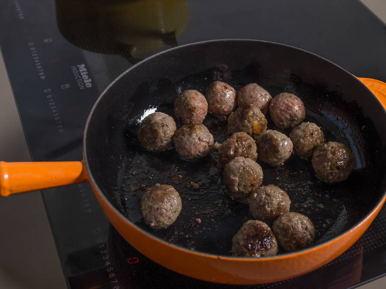 While the meatballs are resting, chop remaining shallots and garlic and sauté in a saucepan with some of the olive oil. Add the crushed tomatoes, season with salt and pepper, and let it simmer. Heat remaining olive oil in the other large frying pan and fry meatballs on all sides for approx. 5 min., or until browned on all sides. Remove from heat and transfer to the tomato sauce. Let simmer for approx. 15 – 20 min.