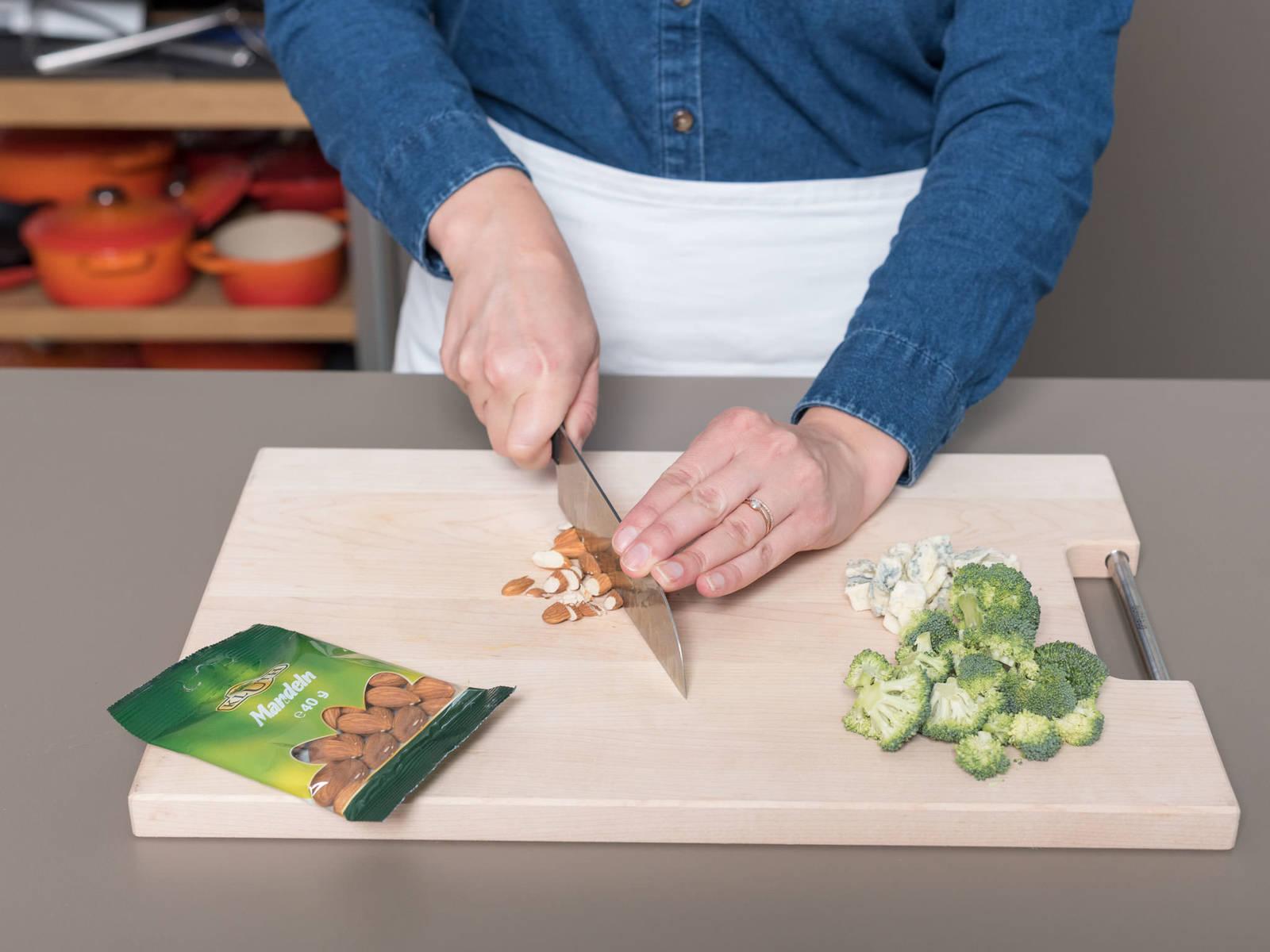 将烤箱预热至230℃。将披萨面团展开,放到铺好烘焙纸的烤盘上。清洗西兰花,切去茎,将其切成小朵。将戈尔根朱勒干酪切成小丁,大略剁碎杏仁。