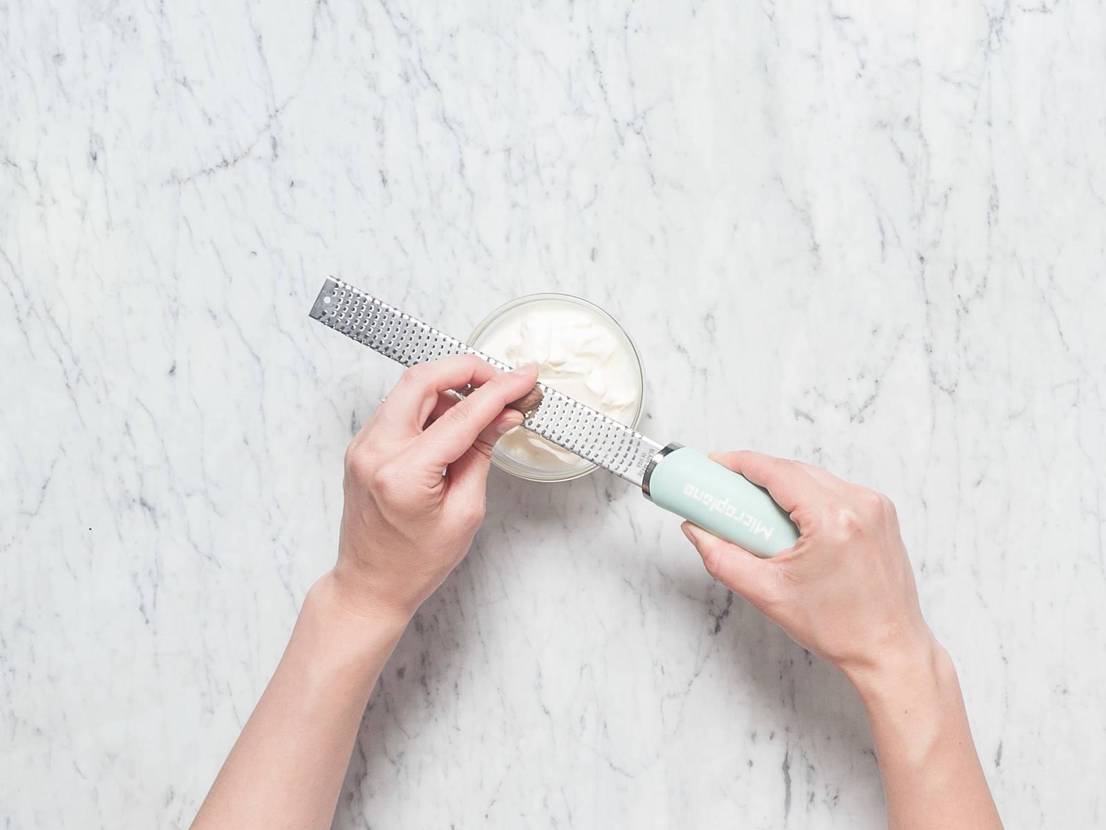 In einer kleinen Rührschüssel Crème fraîche mit Muskat und Pfeffer abschmecken. Schinkenspeck in Würfel schneiden. Zwiebeln in dünne Ringe schneiden. Schnittlauch fein hacken und beiseitestellen.