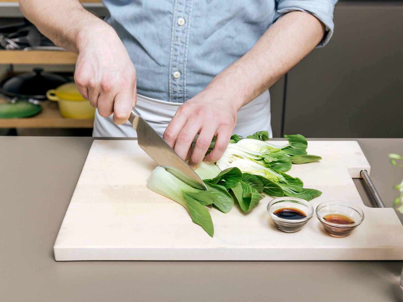 切去白菜两端,然后切成四瓣。在大煎锅中,中高火加热芝麻油。煎白菜4分钟。倒入酱油和一勺鸡肉汤,继续煮。