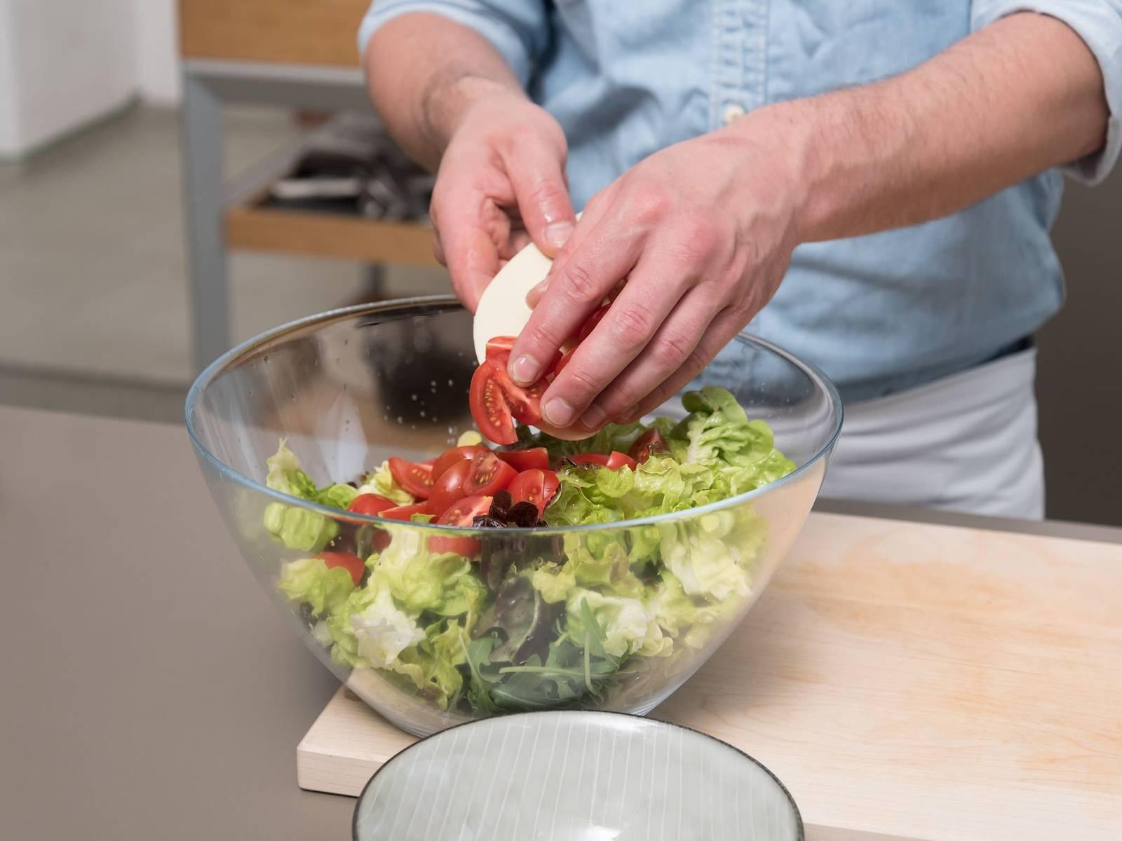 清洗芦笋和生菜,樱桃番茄切成四瓣。将芝麻菜、生菜和番茄放到大搅拌碗中。置于一旁。