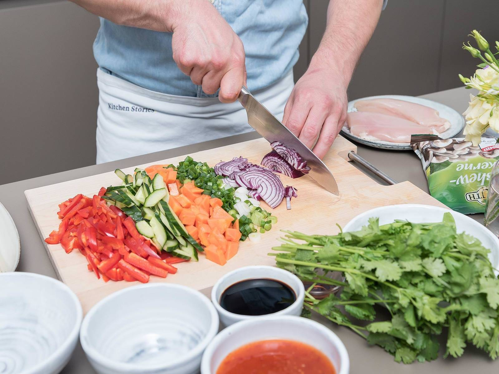 Dice bell pepper and papaya. Chop sugar snap peas. Quarter, deseed, and slice cucumber. Finely slice green onion and mince red onion. Chop cilantro. Transfer all chopped vegetables and herbs, as well as toasted cashews, to a large mixing bowl.