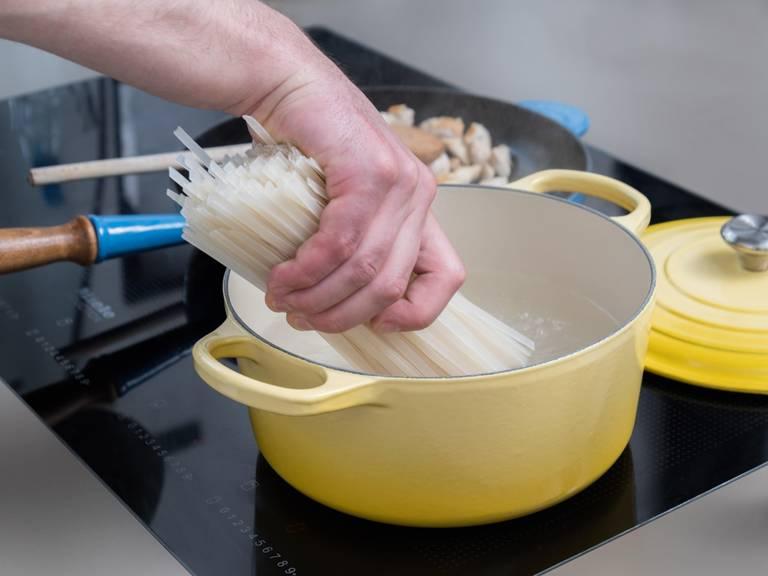 在大平底锅中倒入盐水,煮沸。放入粉丝,煮8-10分钟。滤干后倒入搅拌碗中。