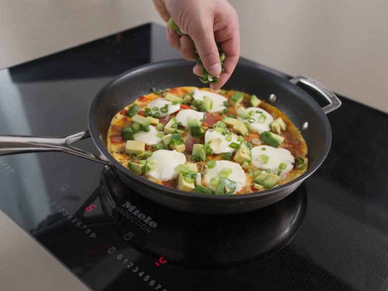 当蛋饼半熟时,均匀地铺上牛油果、马苏里拉奶酪和小葱。再次盖上锅盖至少两分钟至蛋饼全熟。佐以欧芹,开始享用吧!