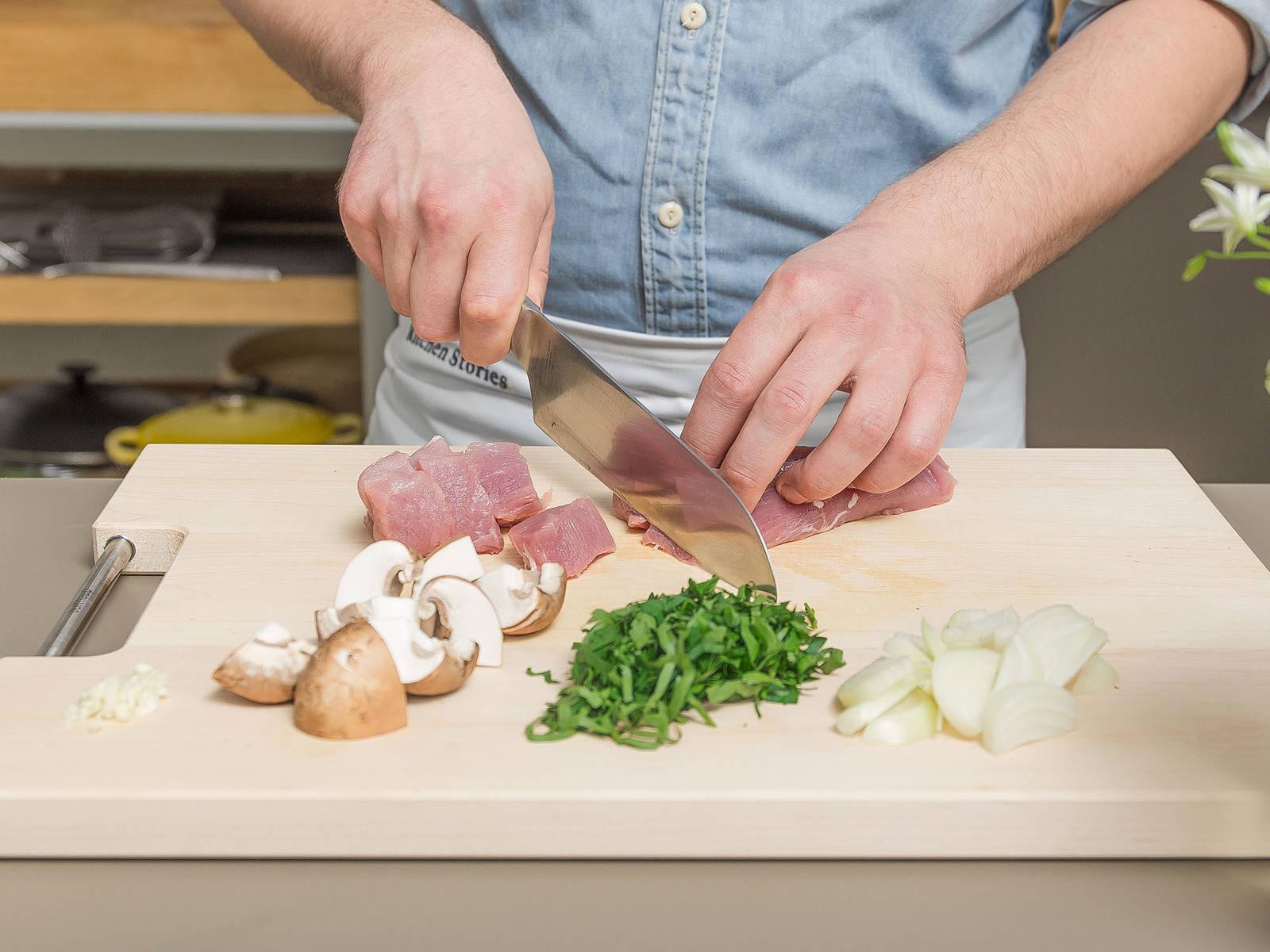 粗略地切碎欧芹,放置一旁。清洗蘑菇并切块,洋葱和蒜剥皮后切丁。修剪猪里脊肉,将其切成均等的大小。