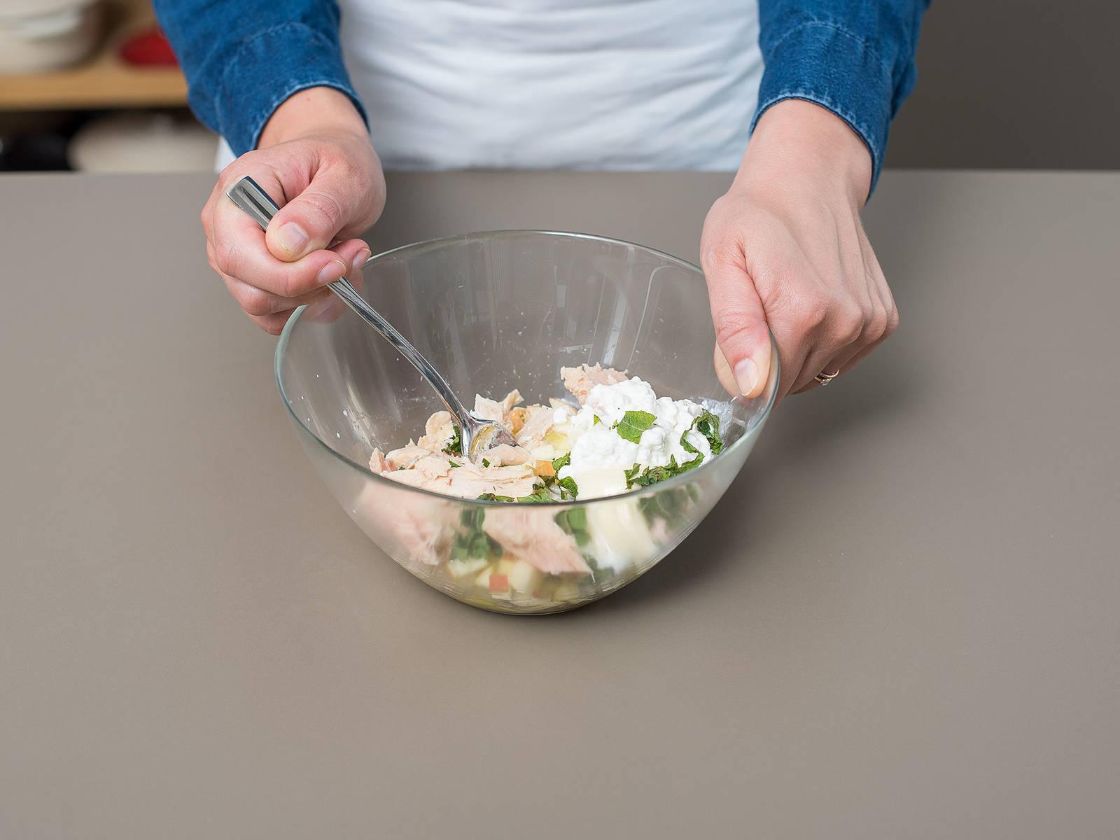 Apfel, Zwiebel, Essiggurken, Minze, Kapern, Hüttenkäse, Mayonnaise und Essig in einer Rührschüssel vermengen. Thunfisch abgießen und untermischen. Mit Salz und Pfeffer abschmecken und ca. 10 Min. ziehen lassen.