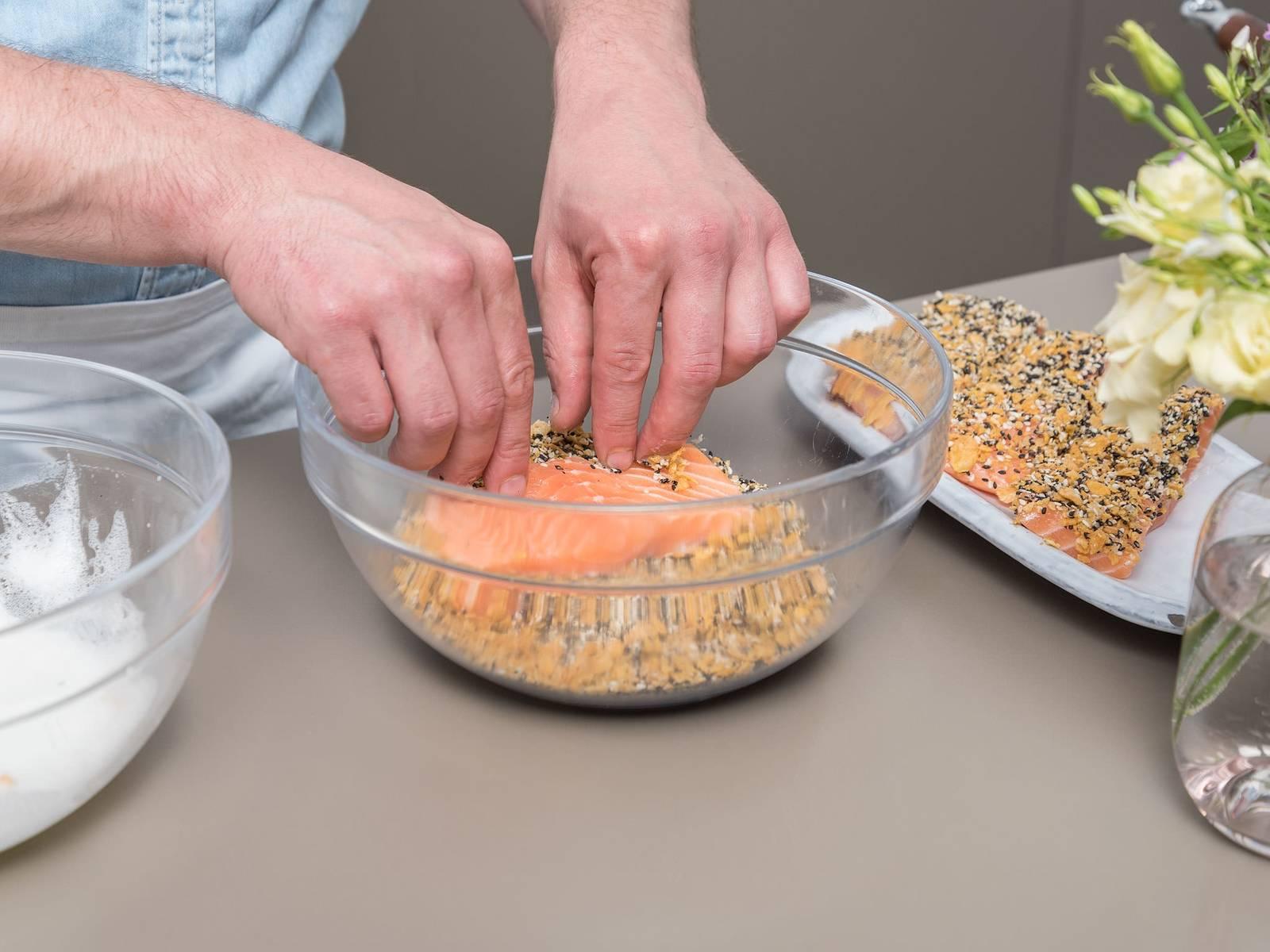 Backofen auf 120°C vorheizen. Cornflakes in eine Plastiktüte geben und zerkleinern. Sesam in einer Pfanne ca. 2 Min. rösten und anschließend in eine Rührschüssel geben. Cornflakes dazugeben und vermengen. Eiweiß in eine zweite Rührschüssel geben und aufschlagen. Oberseite der Lachsfilets erst in Eiweiß tunken und anschließend mit Sesam-Cornflakes-Mischung bedecken.