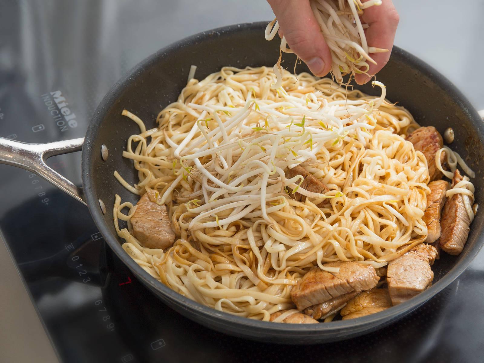 在大煎锅中,中高火加热剩余的植物油。倒入猪里脊,翻炒3分钟。加入煮好的鸡蛋面和酱汁,翻炒均匀,约2分钟,然后调至小火。放入豆芽和青葱,翻炒均匀。撒上更多青葱,尽情享用吧!